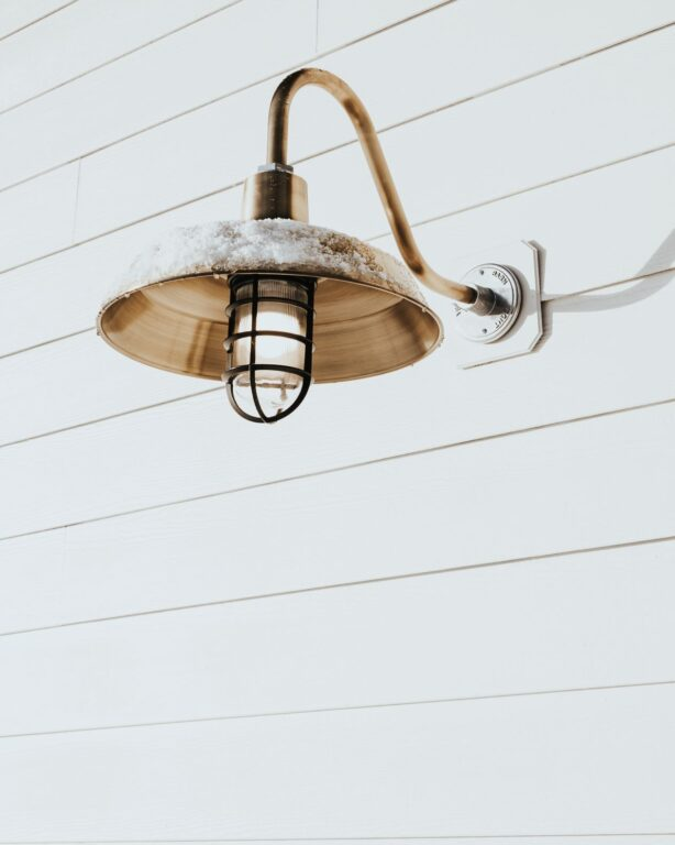 Original Gooseneck Barn Light in Weathered Brass on a White Slatted Exterior