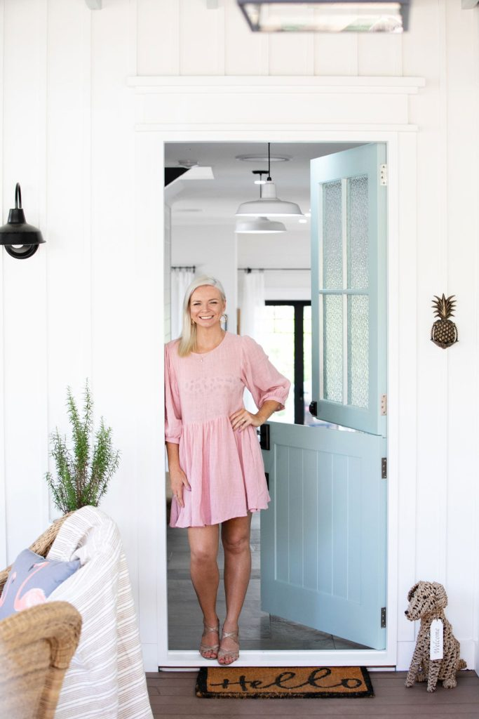 Woman standing in front of teal american styled front door