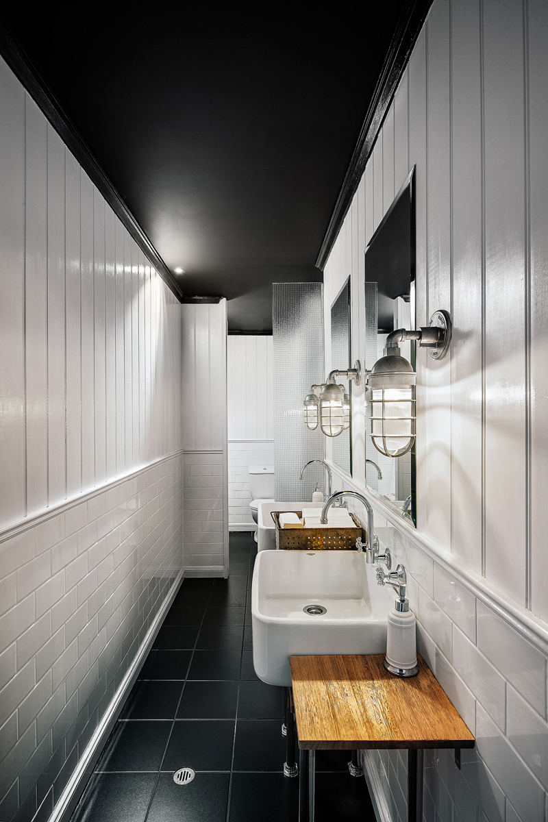 Atomic Industrial Guard Sconces in Long White Bathroom